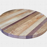Round cutting board made out of mixed solid wood.